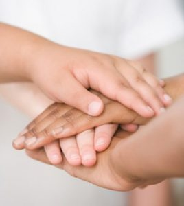 multi-ethnic children's hands resting on each other